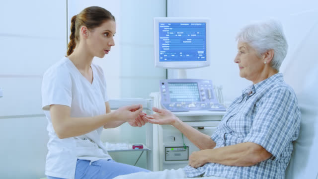 nurse taking blood from the finger of a senior woman - care stock videos & royalty-free footage