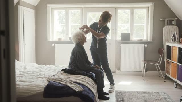 nurse taking care of senior woman at home - bathrobe stock videos & royalty-free footage