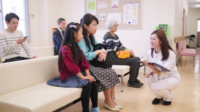 nurse taking little girl and her mother into the doctor's office - mixed age range stock videos & royalty-free footage
