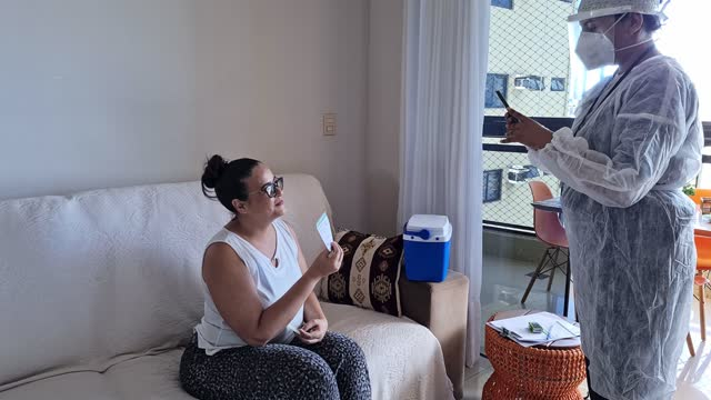 nurse taking picture of mature woman showing her immunization record card after being vaccinated at home - pardo brazilian stock videos & royalty-free footage