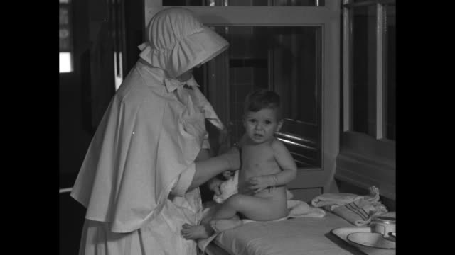 Nurse taking pulse of baby lying in bed / Catholic nun uses towel to wipe off baby as baby sits on table / indistinct shot / posters on wall in...
