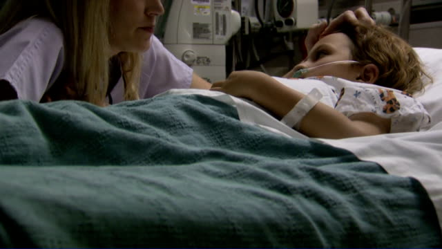 nurse talking to and comforting child in hospital bed - atemhilfe stock-videos und b-roll-filmmaterial