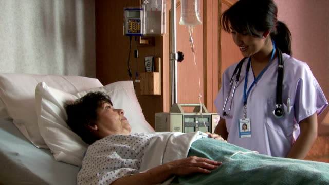 nurse talking to mature woman in hospital bed - brechreiz stock-videos und b-roll-filmmaterial