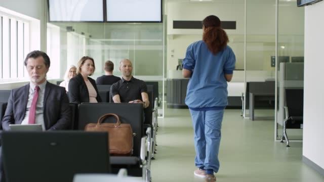 sjuk sköterska pratar med patienter i väntrum - väntrum bildbanksvideor och videomaterial från bakom kulisserna