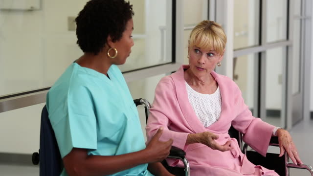 ms tu nurse talking to senior patient sitting in wheelchair / richmond, virginia, usa - scrubs stock videos & royalty-free footage