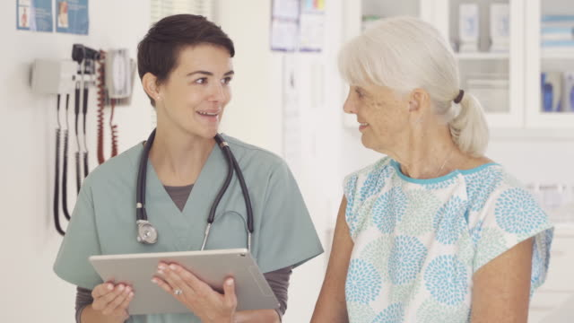 nurse talking to senior patient - human age stock videos & royalty-free footage