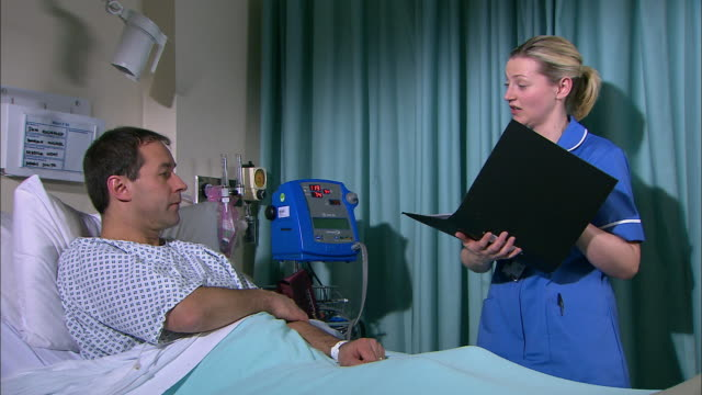 nurse talking with a patient - examination gown stock videos & royalty-free footage