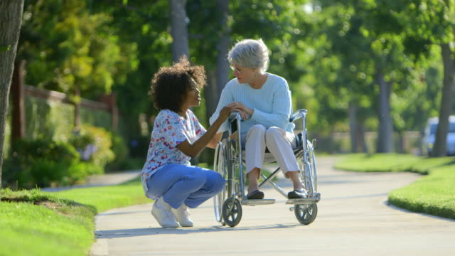 nurse talking with elderly woman in wheelchair - scrubs stock videos & royalty-free footage