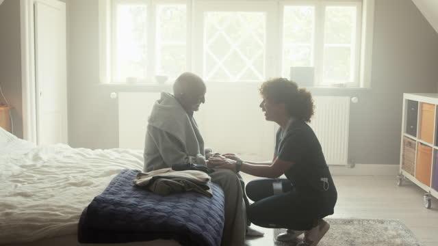 nurse talking with senior man - bathrobe stock videos & royalty-free footage