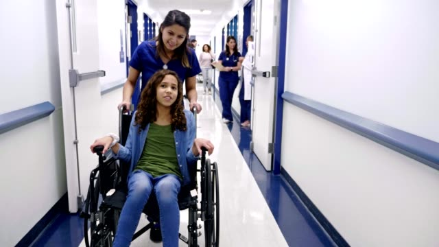 nurse talks with female preteen patient as she pushes the girl in the wheelchair - leaving hospital stock videos & royalty-free footage