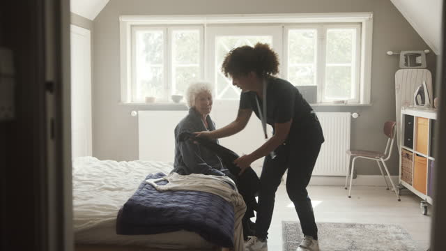 nurse telling senior woman to choose clothes - bathrobe stock videos & royalty-free footage