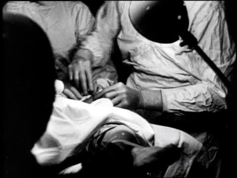 vidéos et rushes de nurse tends to i.v / surgeon cuts patient / nurse stands at patients head / doctor sits next to patient / i.v. drips - operating