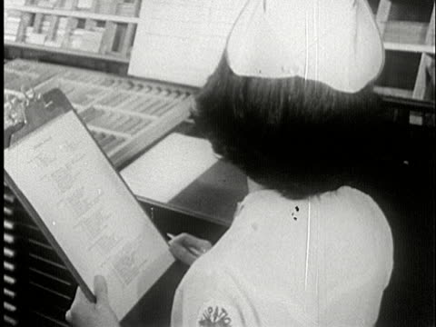 vidéos et rushes de ms, b/w, nurse ticking list on clipboard, usa - bloc note
