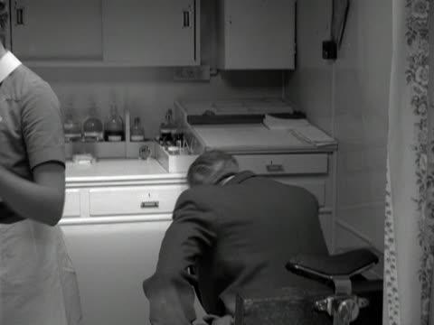 vidéos et rushes de a nurse treats a patient's bandaged finger in a mobile doctors' surgery 1960 - pansement médical
