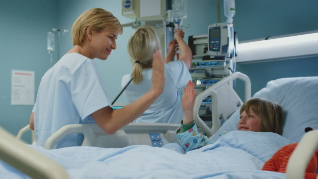 nurse visiting boy lying on bed in emergency room - nurse stock videos & royalty-free footage