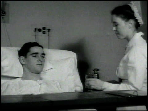 vidéos et rushes de nurse w/ by bedside of young adult 'charlie abbott' giving him pill & water. flashback: 'charlie abbott' at 7 years old, mother taking care of him,... - comprimés