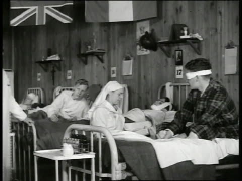 Nurse w/ in wooden barracks w/ soldiers in numbered beds MS Soldier w/ eye bandaged 'Congressman John Lawton' visiting wounded soldier