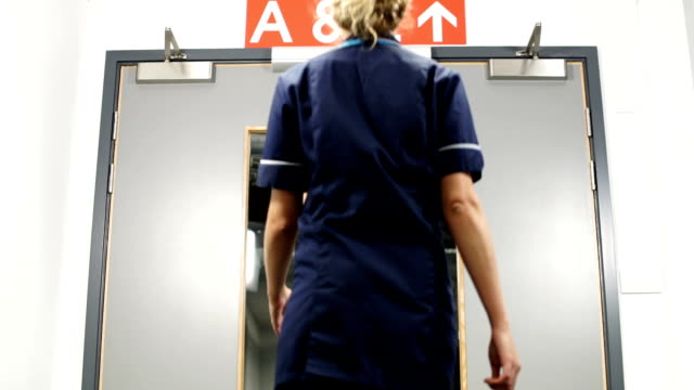 nurse walks through hospital doors toward a and e low angle - nhs stock-videos und b-roll-filmmaterial