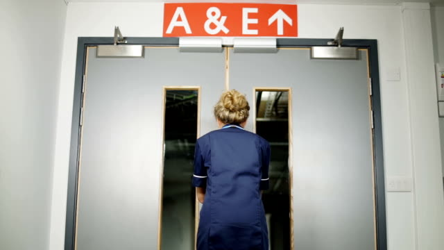 nurse walks through hospital doors toward a&e low angle - casualty stock videos & royalty-free footage