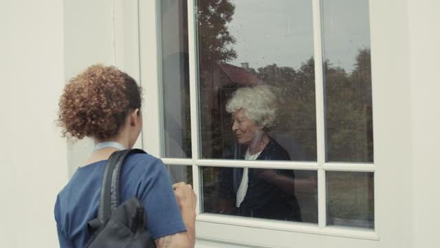 nurse waving at senior woman - healthcare worker stock videos & royalty-free footage