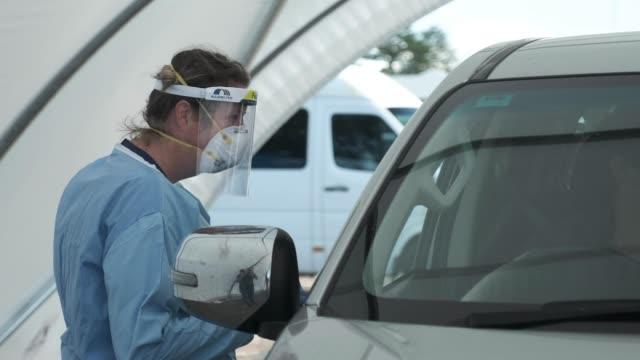 nurse wearing a mask greets a car entering the drive-through coronavirus testing clinic on april 6, 2020 in sydney, australia. nsw health authorities... - home economics点の映像素材/bロール