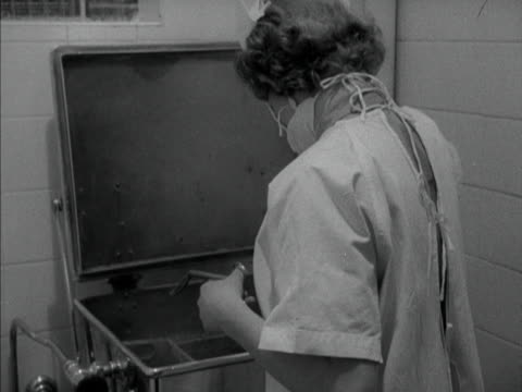 a nurse wearing a mask removes medical equipment from a sterilizer 1958 - untersuchungskittel stock-videos und b-roll-filmmaterial