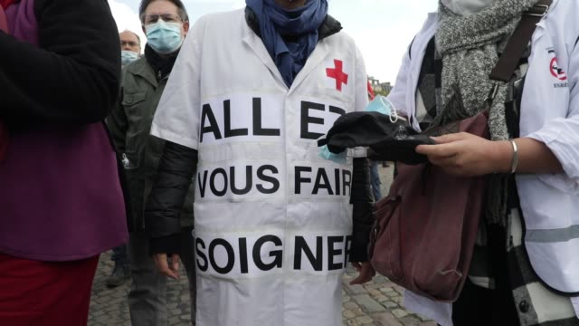 """nurse wears a gown on which it is written """"go get treatment"""" during a day of mobilization and national strike in the health, medico-social and social... - rettungsdienst mitarbeiter stock-videos und b-roll-filmmaterial"""