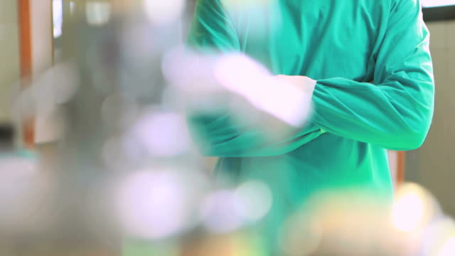nurse with arms crossed while wearing surgical clothes - chirurgenkappe stock-videos und b-roll-filmmaterial