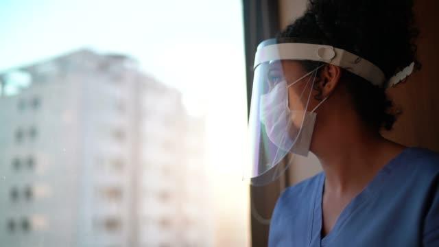 krankenschwester mit schützender gesichtsmaske, die durch das fenster im krankenhaus schaut - hoffnung stock-videos und b-roll-filmmaterial