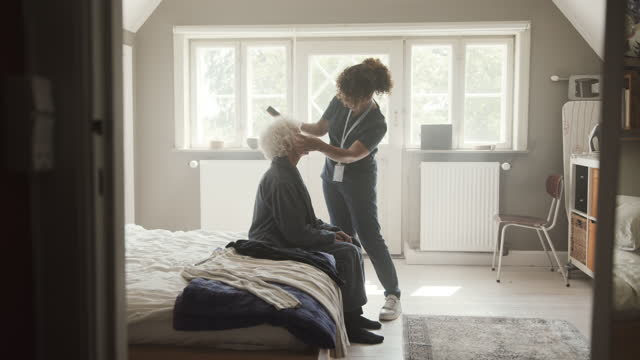 nurse with senior woman in bedroom - bathrobe stock videos & royalty-free footage