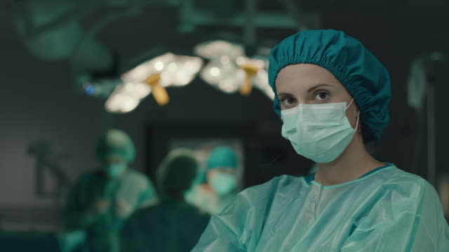 nurse with surgery mask on face - surgeon stock videos & royalty-free footage