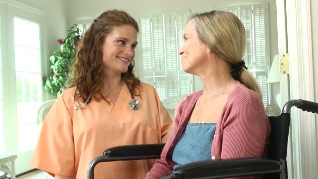 vídeos de stock e filmes b-roll de enfermeira com cadeira de rodas mulher em casa limite - chamada a casa