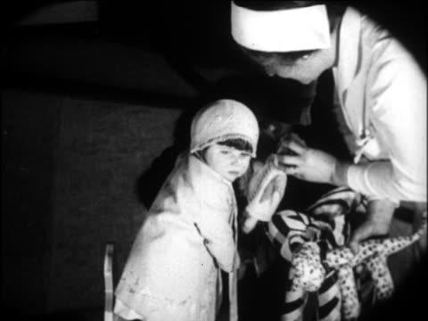 b/w 1924 nurse + woman handing little girl doll / newsreel - 1924 stock-videos und b-roll-filmmaterial