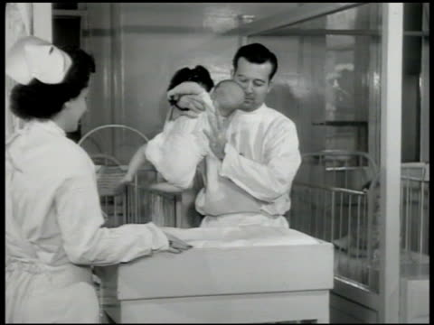 nurse working in room w/ babies, children in cribs. one child standing in crib w/ something in mouth. doctor giving baby checkup, nurse helping. baby... - strumento medico video stock e b–roll
