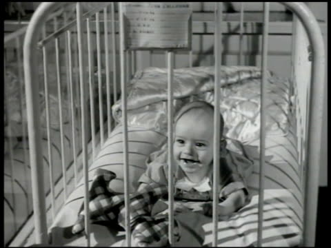 stockvideo's en b-roll-footage met nurse working in room w/ babies in cribs picking up baby baby on stomach in crib smiling baby standing in crib holding onto side black baby sitting... - 1946