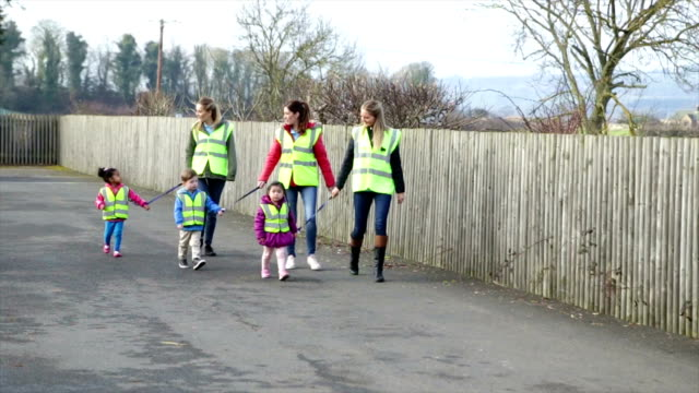 nursery group walking with children wearing safety straps - footpath stock videos & royalty-free footage