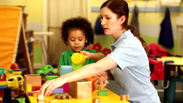 nursery worker supervising child playing with toys - child care stock videos & royalty-free footage