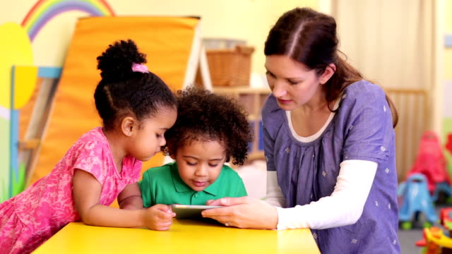 nursery worker teaching children how to use a digital tablet - nursery school child stock videos & royalty-free footage