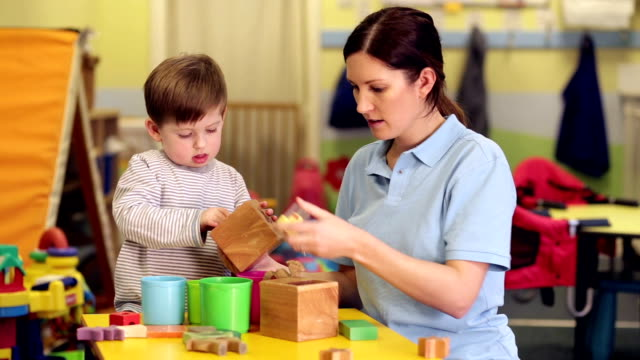 nursery worker with child playing with toys - child care stock videos & royalty-free footage