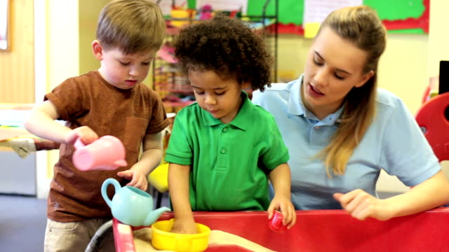 nursery workers with children playing in the sandpit - preschool student stock videos and b-roll footage