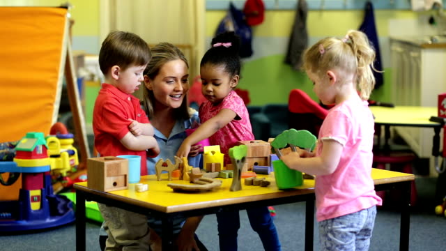 Nursery workers with children playing with toys