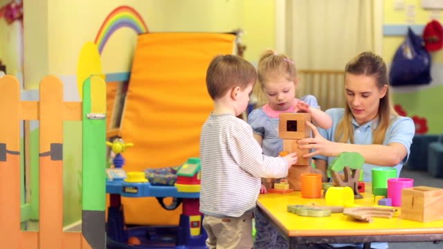 nursery workers with children playing with toys - barnomsorg bildbanksvideor och videomaterial från bakom kulisserna