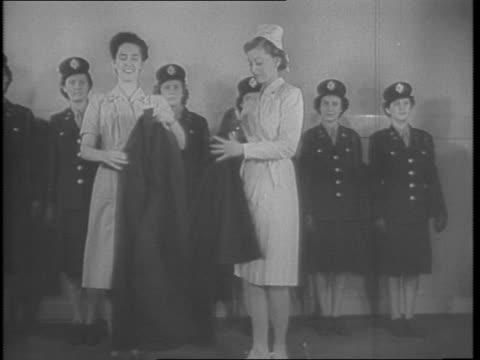 nurses at fort meade model new nurses uniforms / nurses lined up on a field wearing helmets and coveralls closeups / running across field falling to... - jumpsuit stock videos & royalty-free footage