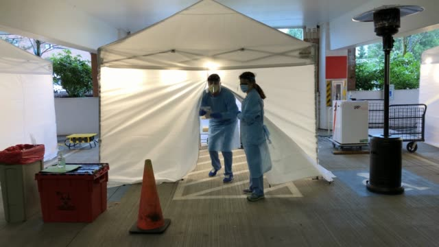 stockvideo's en b-roll-footage met nurses check registration lists before testing patients for coronavirus at the university of washington medical center on march 13, 2020 in seattle,... - staat washington