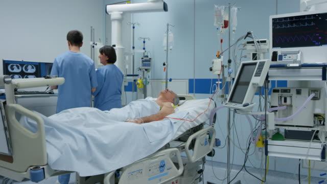 ds infermiere controllare gli studenti maschi pazienti in terapia intensiva - reparto di terapia intensiva video stock e b–roll