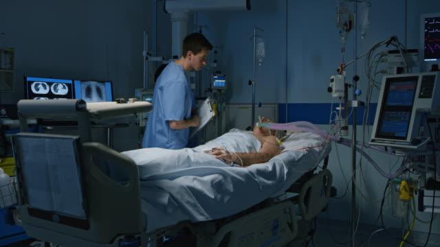 ds infermiere controlla il paziente di terapia intensiva - reparto di terapia intensiva video stock e b–roll