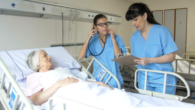Nurses communicating while examining senior woman