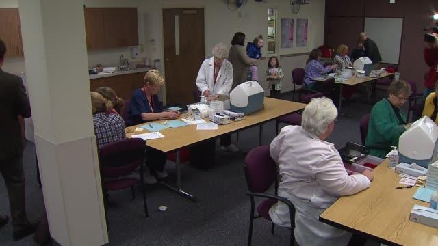 stockvideo's en b-roll-footage met nurses giving h1n1 swine flu vaccinations on october 24, 2013 in chicago, illinois - varkensgriep