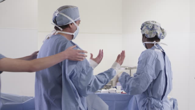 stockvideo's en b-roll-footage met ms nurses helping doctor prepare for surgery / houston, texas, united states - chirurg