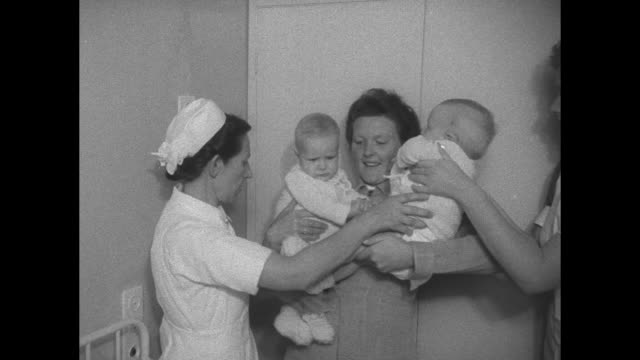 nurses hold formerly conjoined twins folkje de vries and tjitskes de vries / exterior of hospital with netherlands flag / vs twins parents and others... - nurse waving stock videos & royalty-free footage